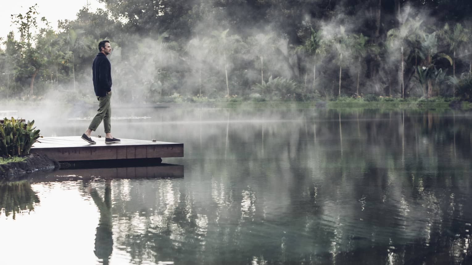 Man walks down a dock as steam rises off the water's surface, his reflection clearly visible