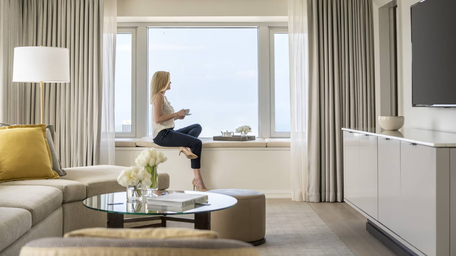 A woman hold a cup of tea and sits on a windowsill in a One Bedroom Suite