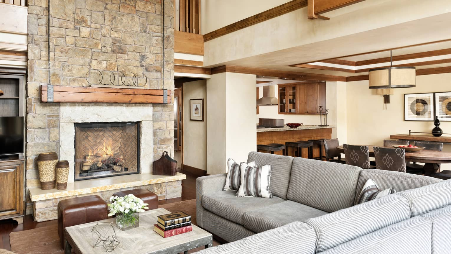 Leather and upholstered sofas, a wooden table, trim, stone fireplace, connected dining room area