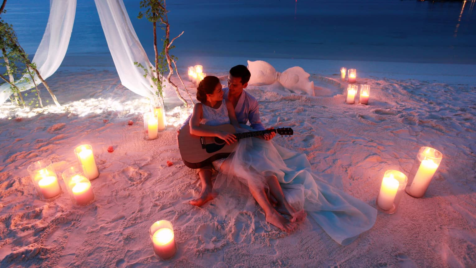 Man and woman hold guitar on sand beach surrounded by candles at night
