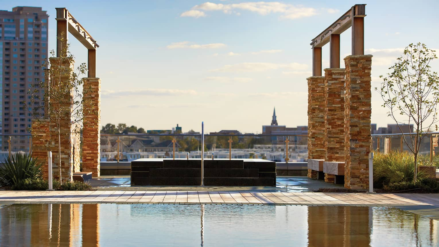 Tall brick pillars, frames over outdoor rooftop whirlpool and reflecting pool