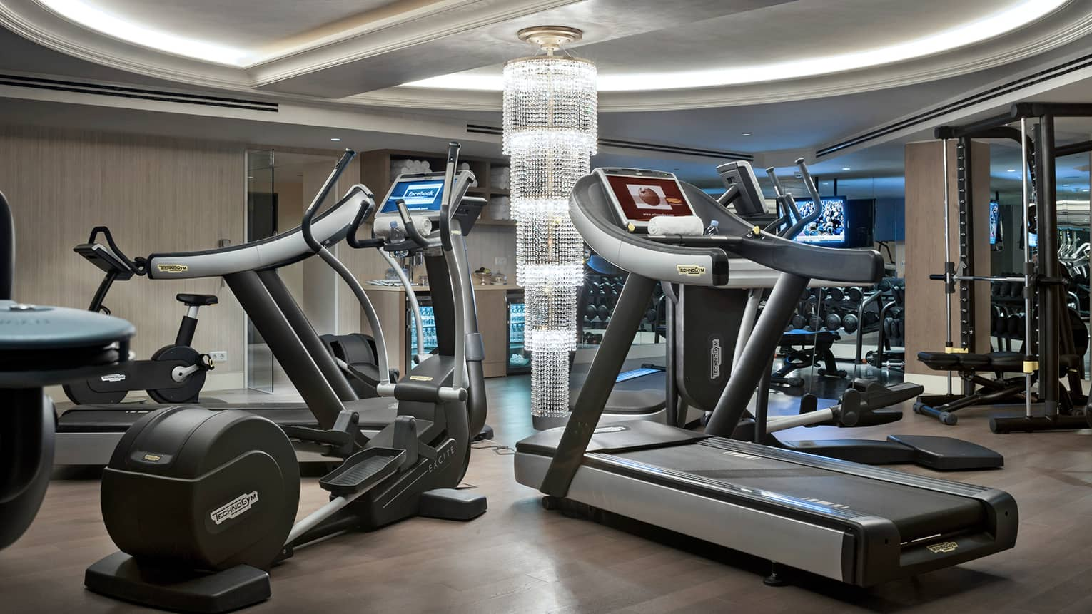 Cardio machines in circle around long crystal chandelier in Fitness Centre