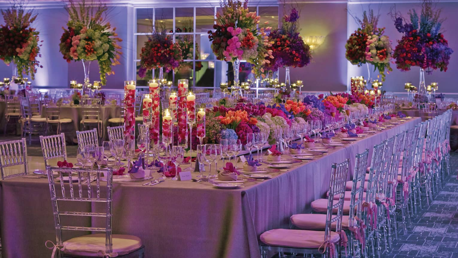Large tropical flower-filled wedding banquet table in candlelit ballroom with purple lights