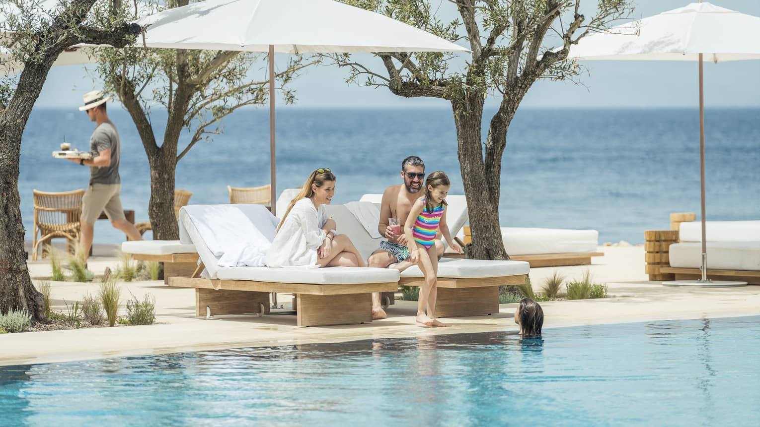 A man and woman sit on white lounge chairs while their two kids play in the pool overlooking the ocean