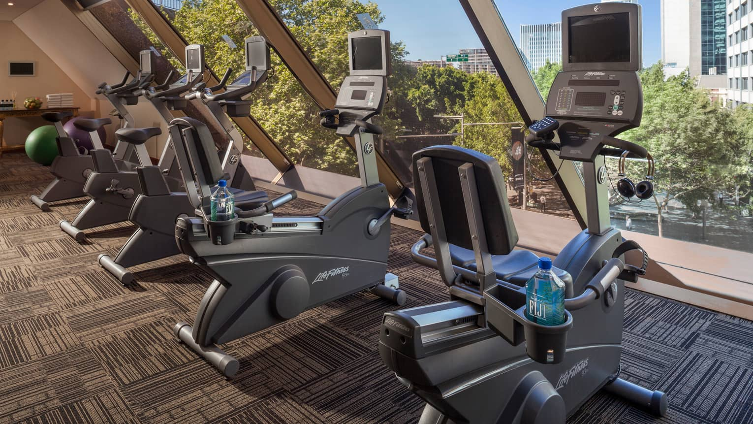 Cardio bikes, machines lined up by window in Fitness Centre