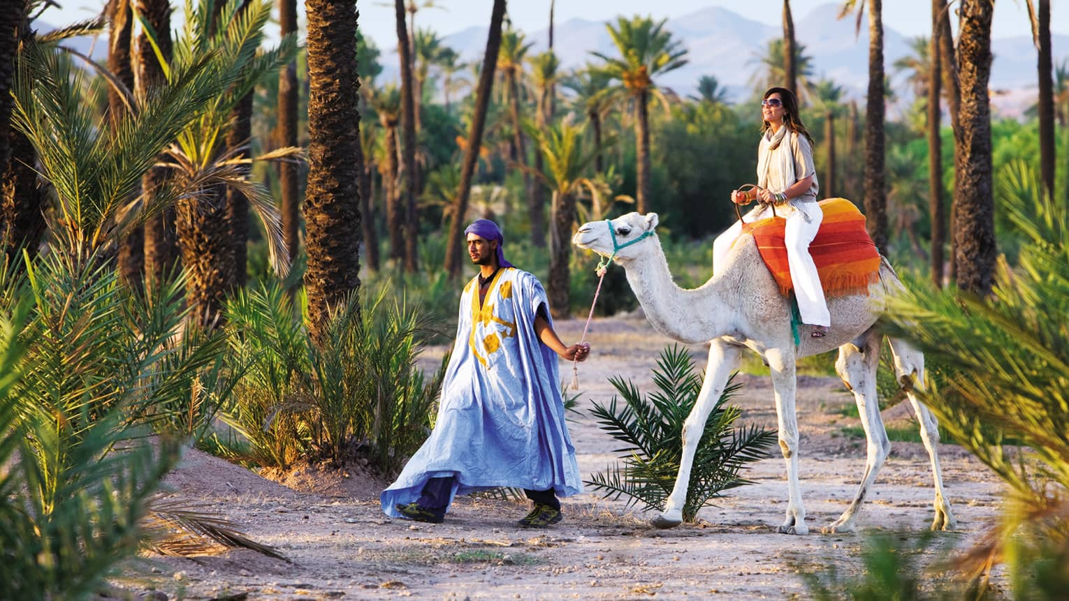 Man leads woman riding camel down sandy path surrounded by palm trees