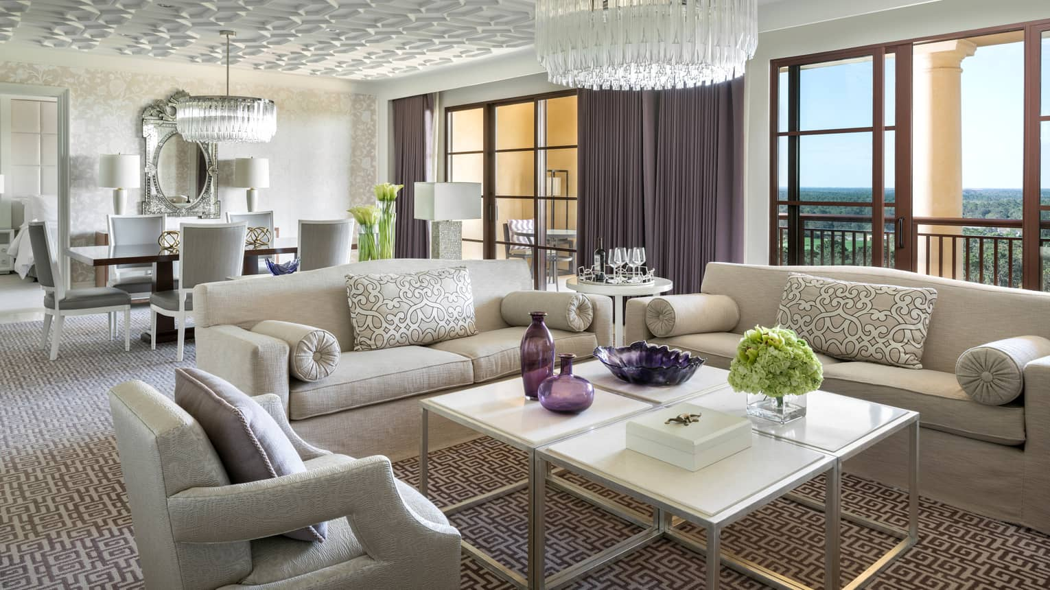 Grand Suite white sofas, armchair around coffee table with purple vases under crystal chandelier, sunny windows