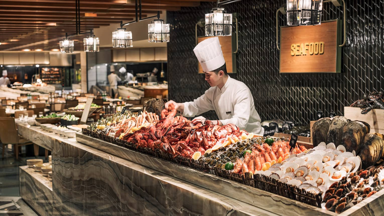 Chef wearing tall white hat arranges fresh lobster, seafood on ice at buffet The Market Kitchen buffet station