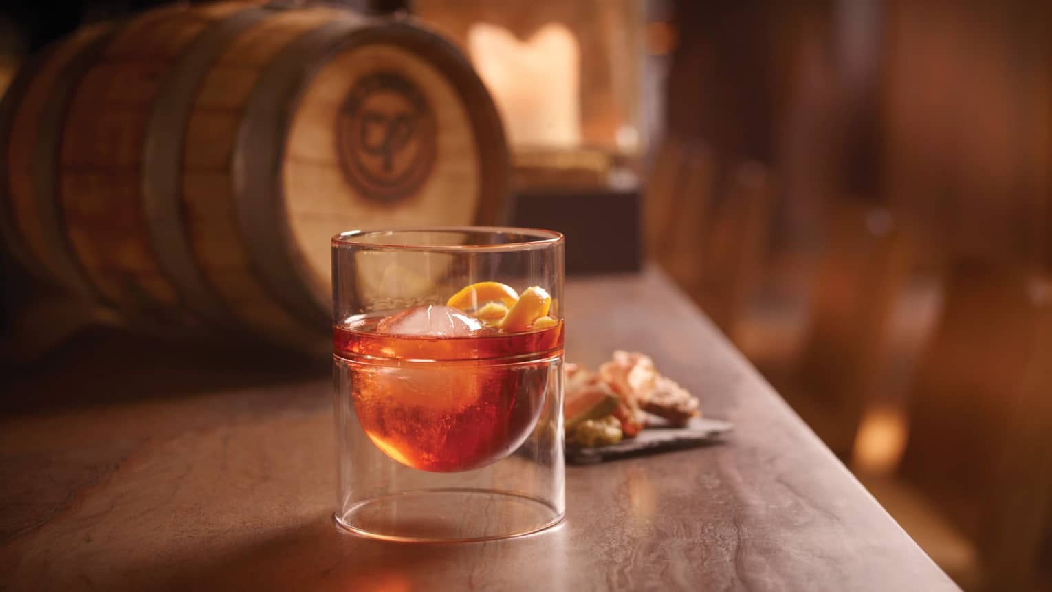 Neo Negroni cocktail in glass with ice, orange peels on wood bar by barrel