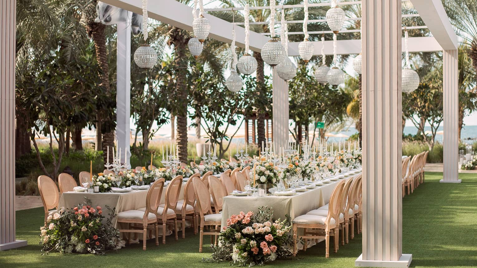 Garden wedding, glass lanterns hang from white pergola over long dining tables