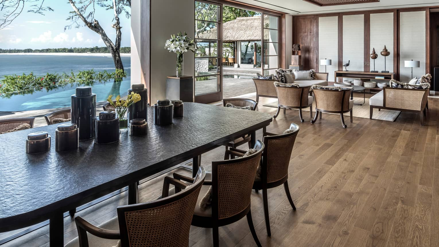 Long private dining table with numerous black vases beside sitting area with wicker furniture, open walls to patio, ocean