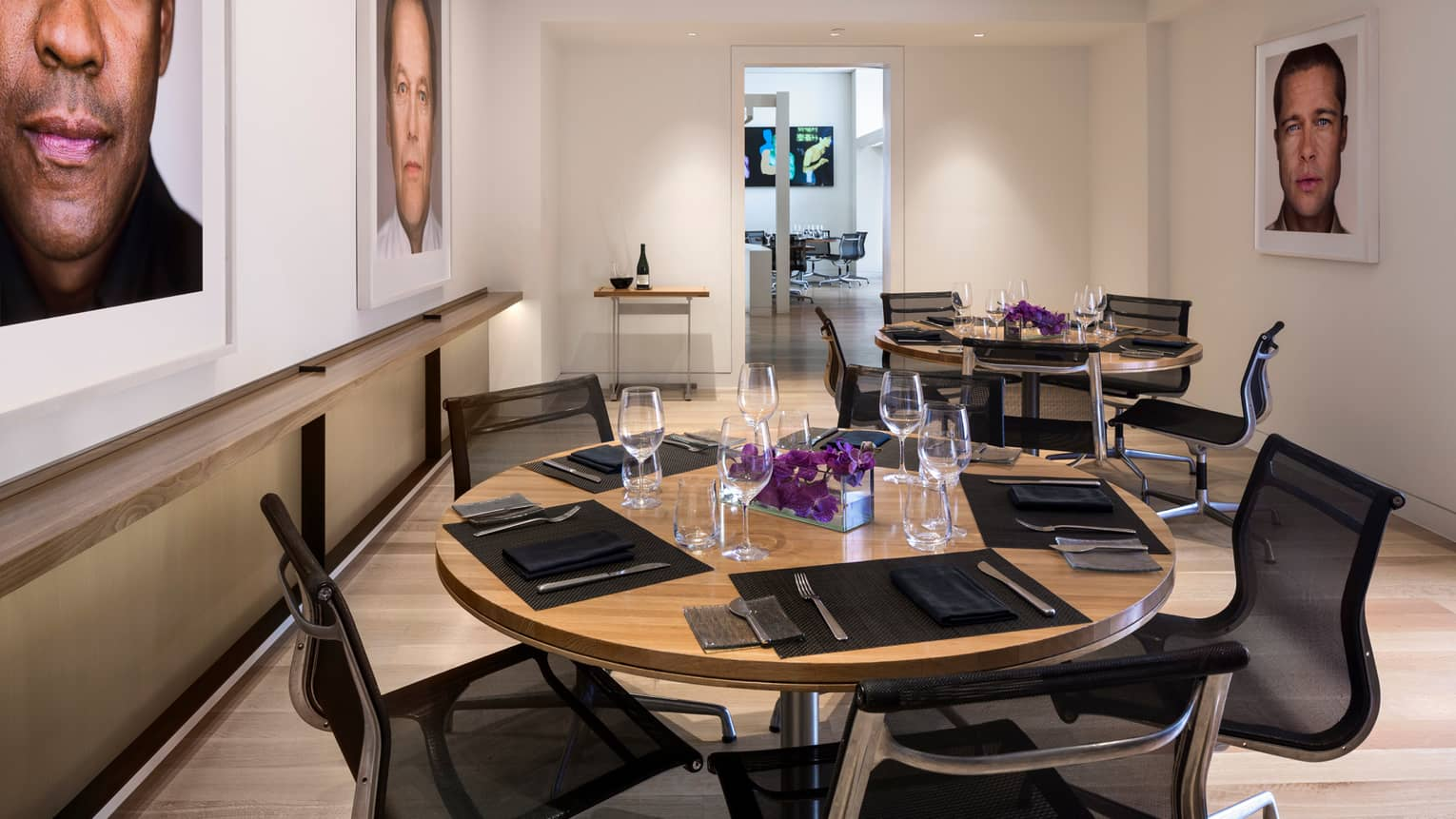 Petit Cut round dining, meeting table under framed prints of Hollywood stars