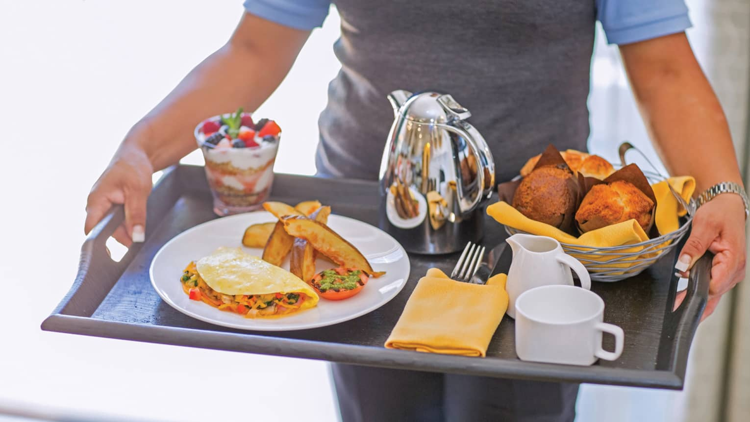 Server carries breakfast tray with omelette, yogurt parfait, basket of muffins, coffee carafe and mugs