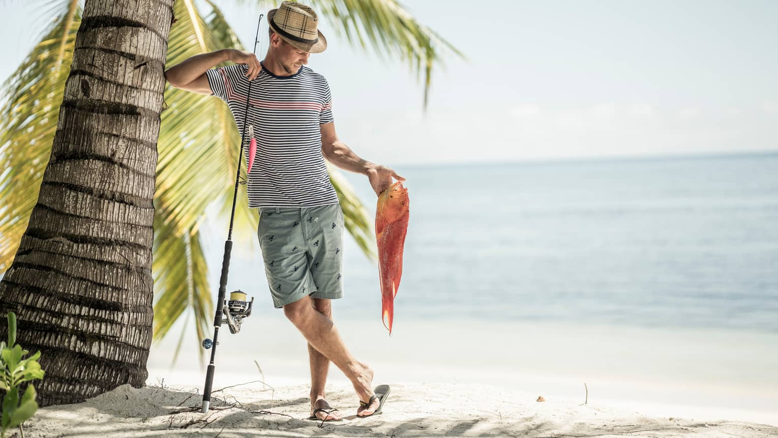 Executive Chef Olivier Barré on the beach, leaning on palm tree while holding a fishing pole and fish