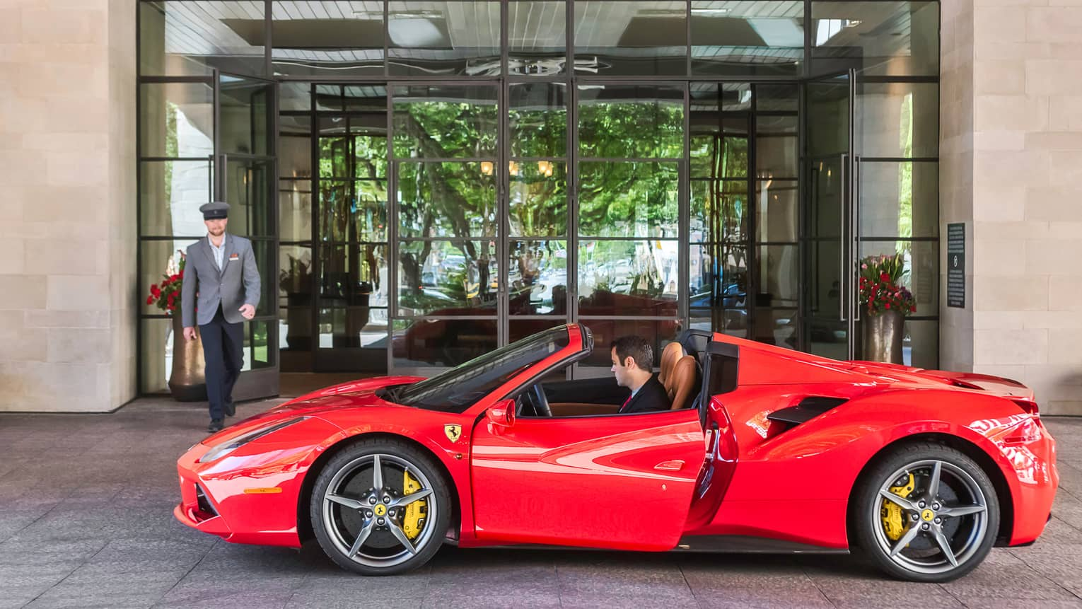 Hotel staff walks towards man in driver's seat of red sports car at Four Seasons Hotel Austin entrance