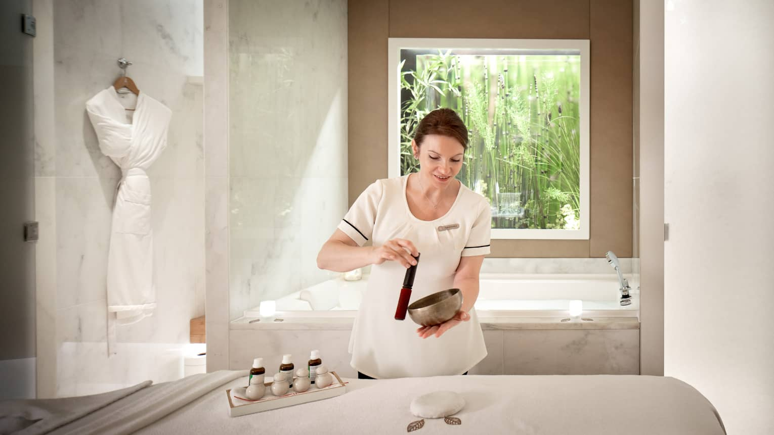 Spa attendant in white top, smiling and using singing bowl beside white spa table, robe and tub in backdrop