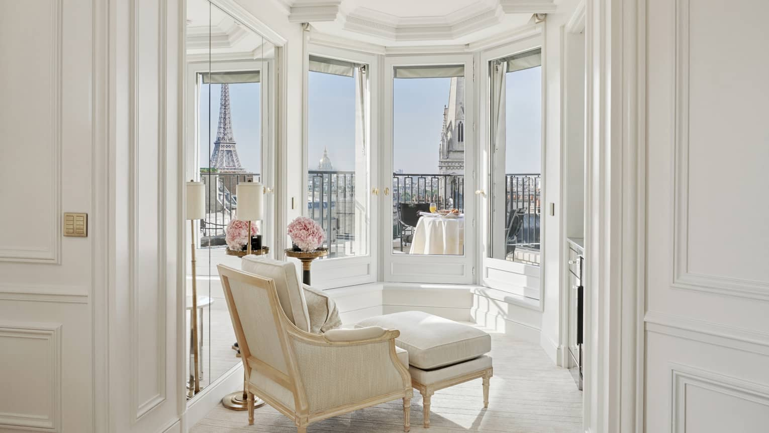 A white room has windows and a balcony with a direct view of the Eiffel Tower