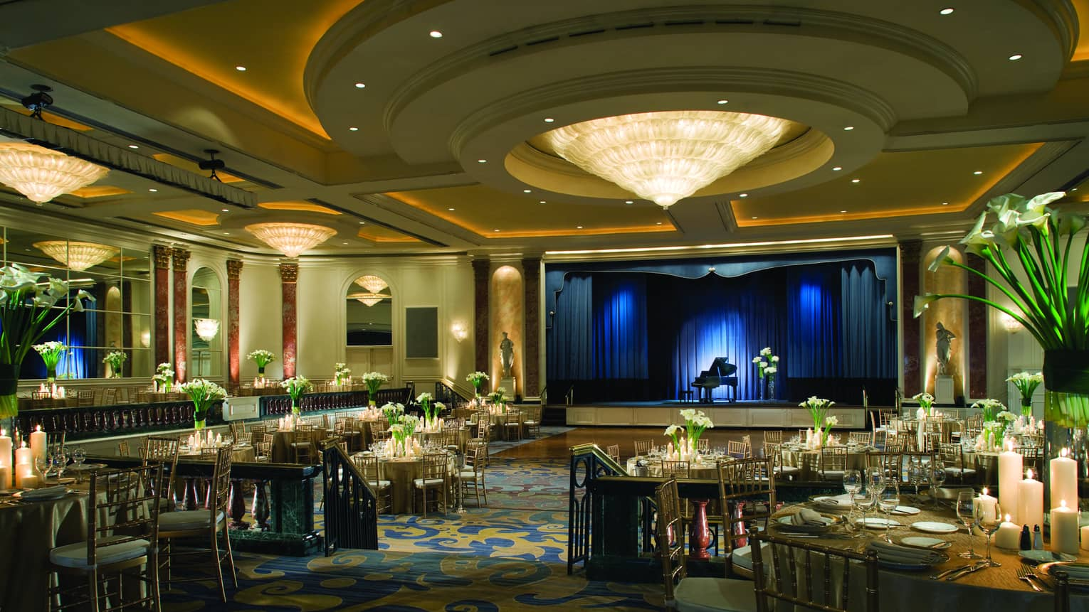 Cone shaped chandelier and round ceiling over banquet room dance floor by stage with baby grand piano, blue lights