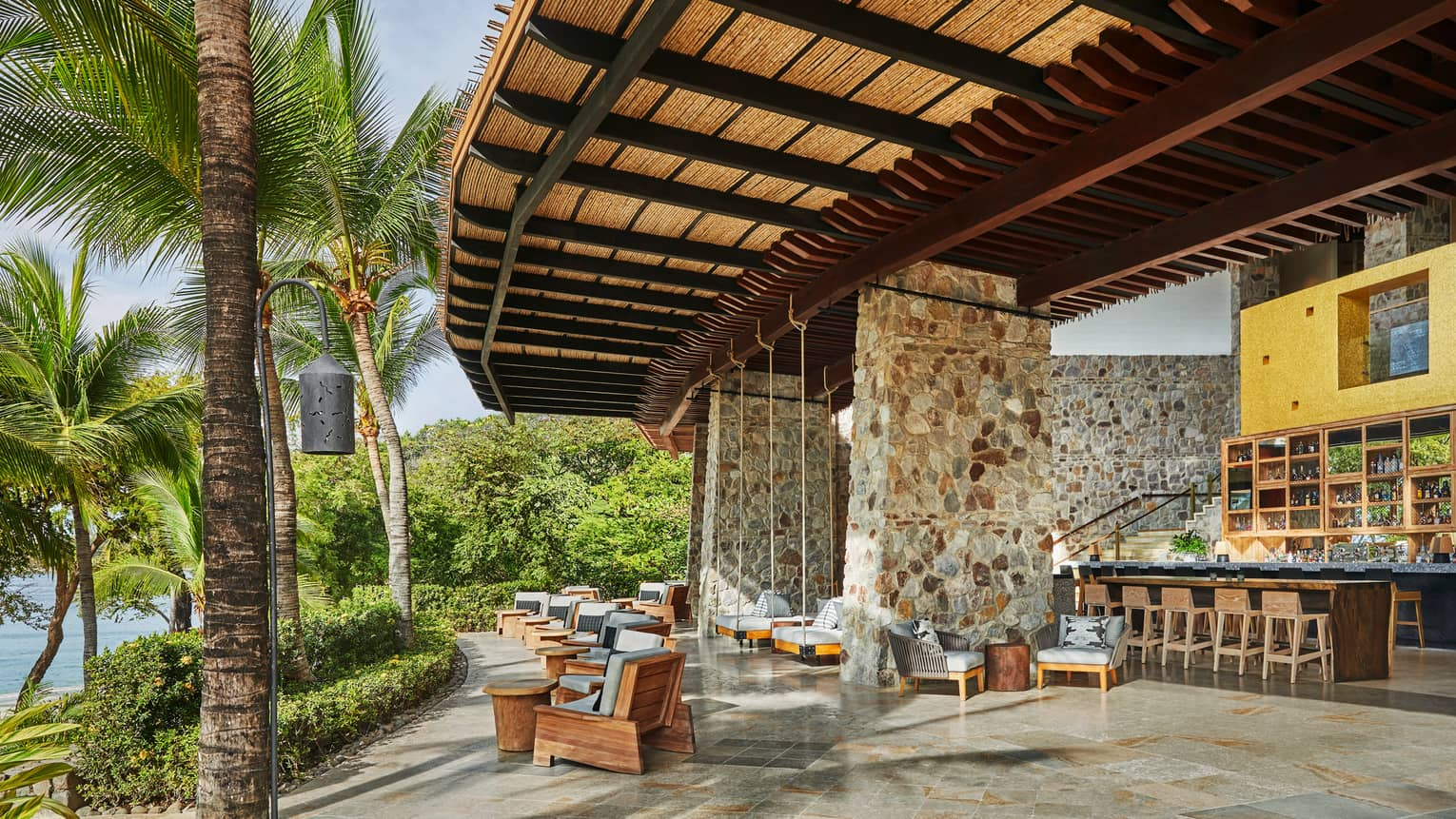 Anejo bar under large stone pillars, curved rattan roof over lounge chairs looking out at palms