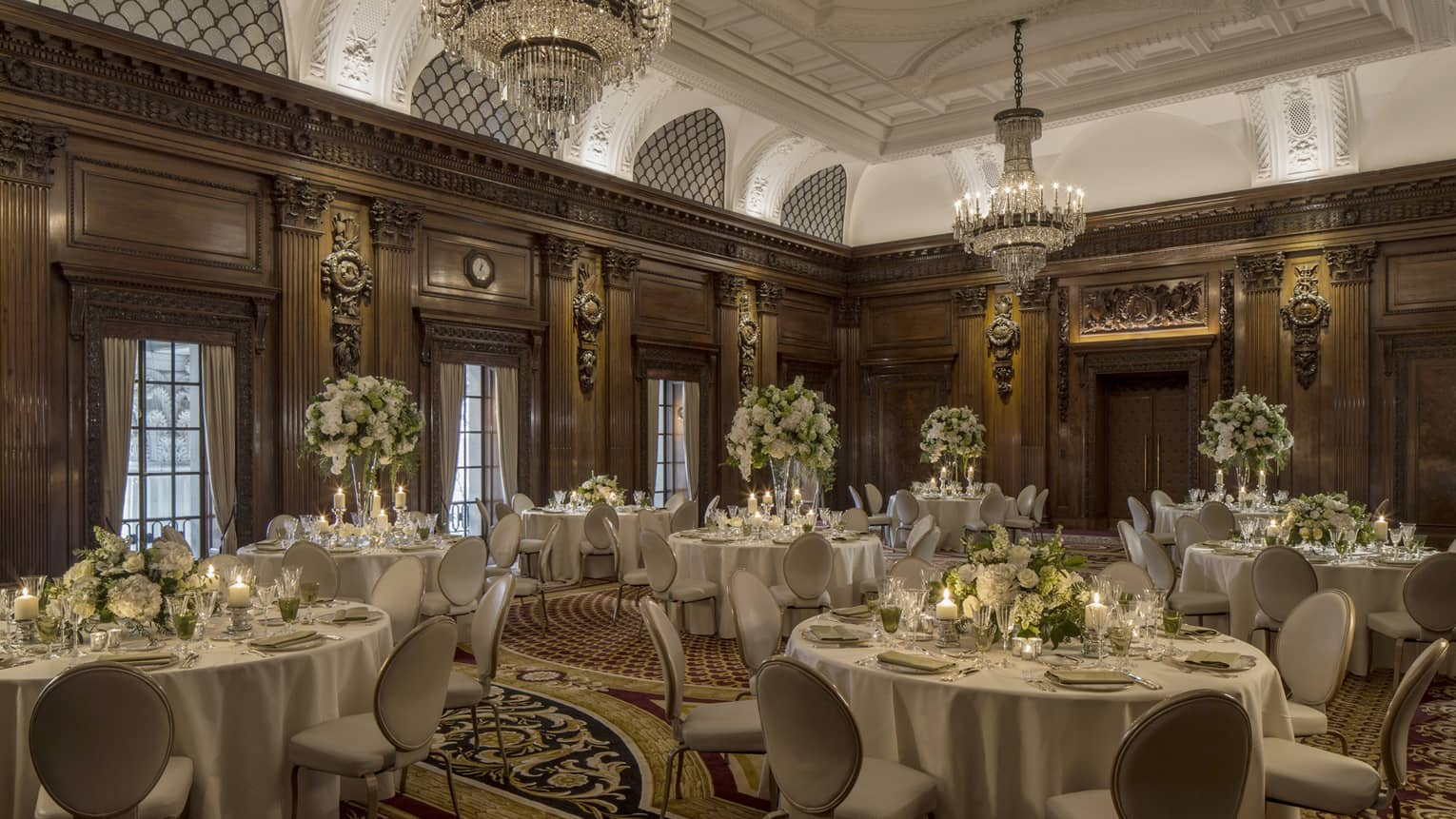Elegant ballroom with decorative wood walls, crystal chandeliers over round banquet dining tables