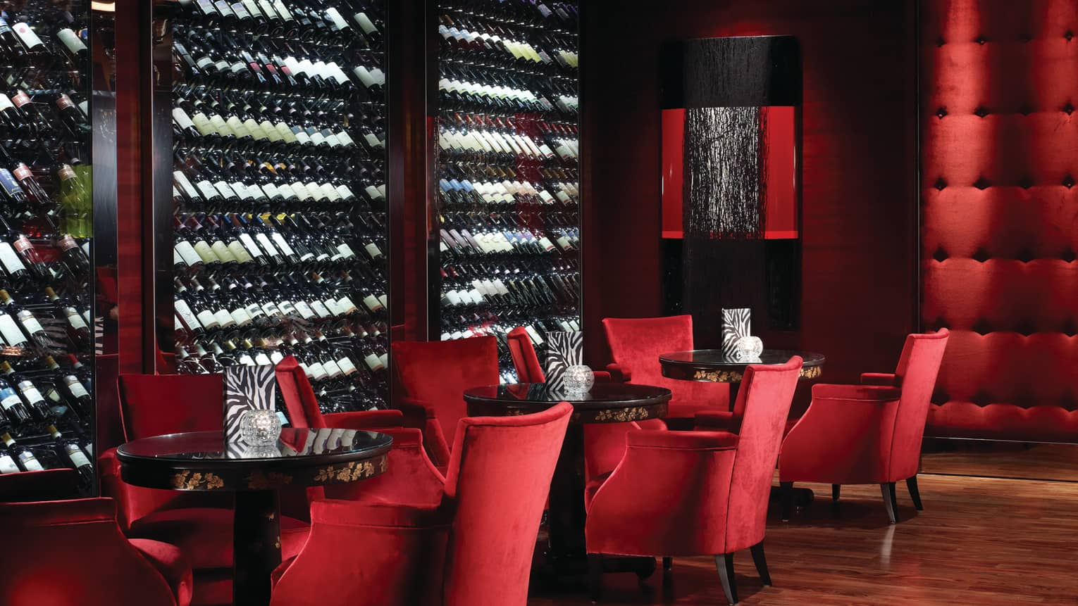 Amaranto Bar red velvet lounge chairs by large glass cellars lined with bottles