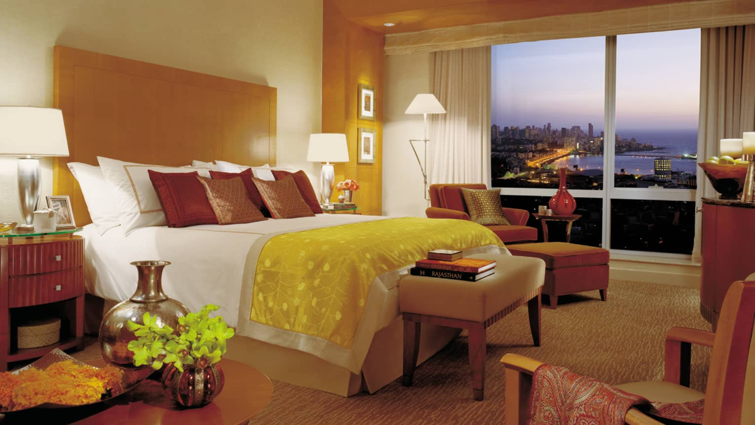 Deluxe Sea-View Room bed with yellow silk blanket, books on bench, chaise by window, sunset