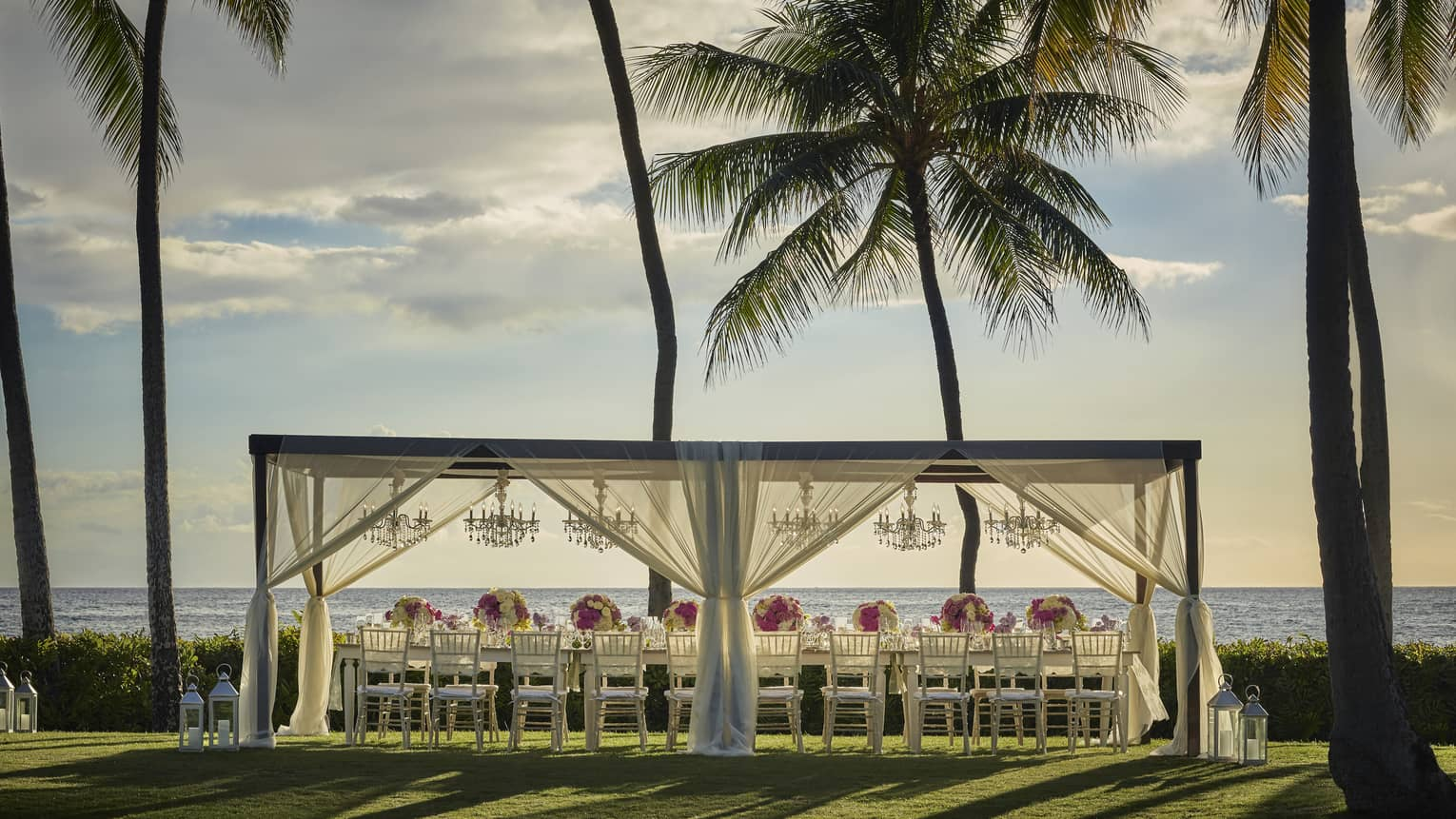Long wedding dining table under pergola with sheer white curtains on lawn by ocean