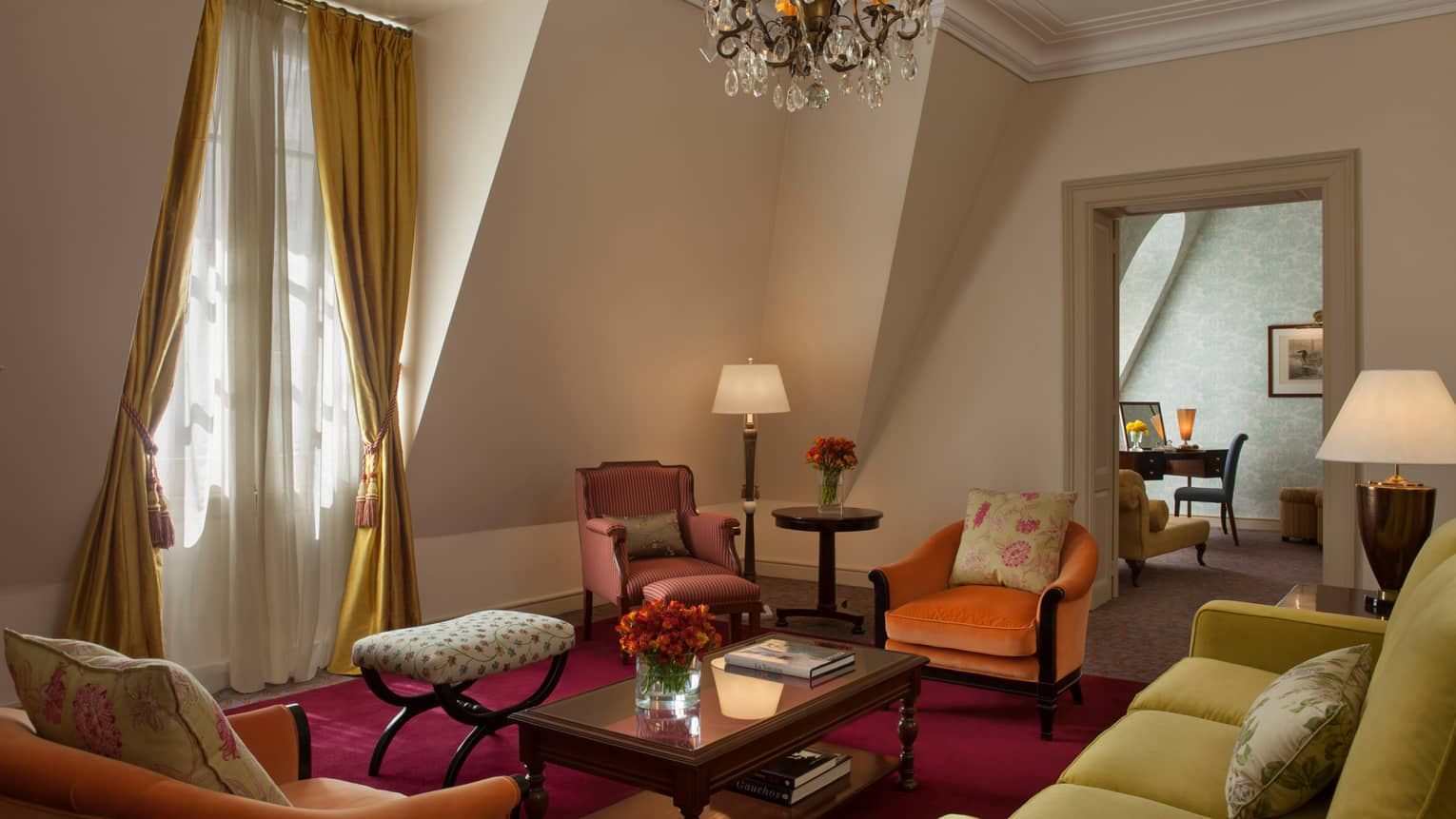 La Mansión Ambassador Suite with pink and orange velvet armchairs, yellow sofa under sloped walls, small crystal chandelier