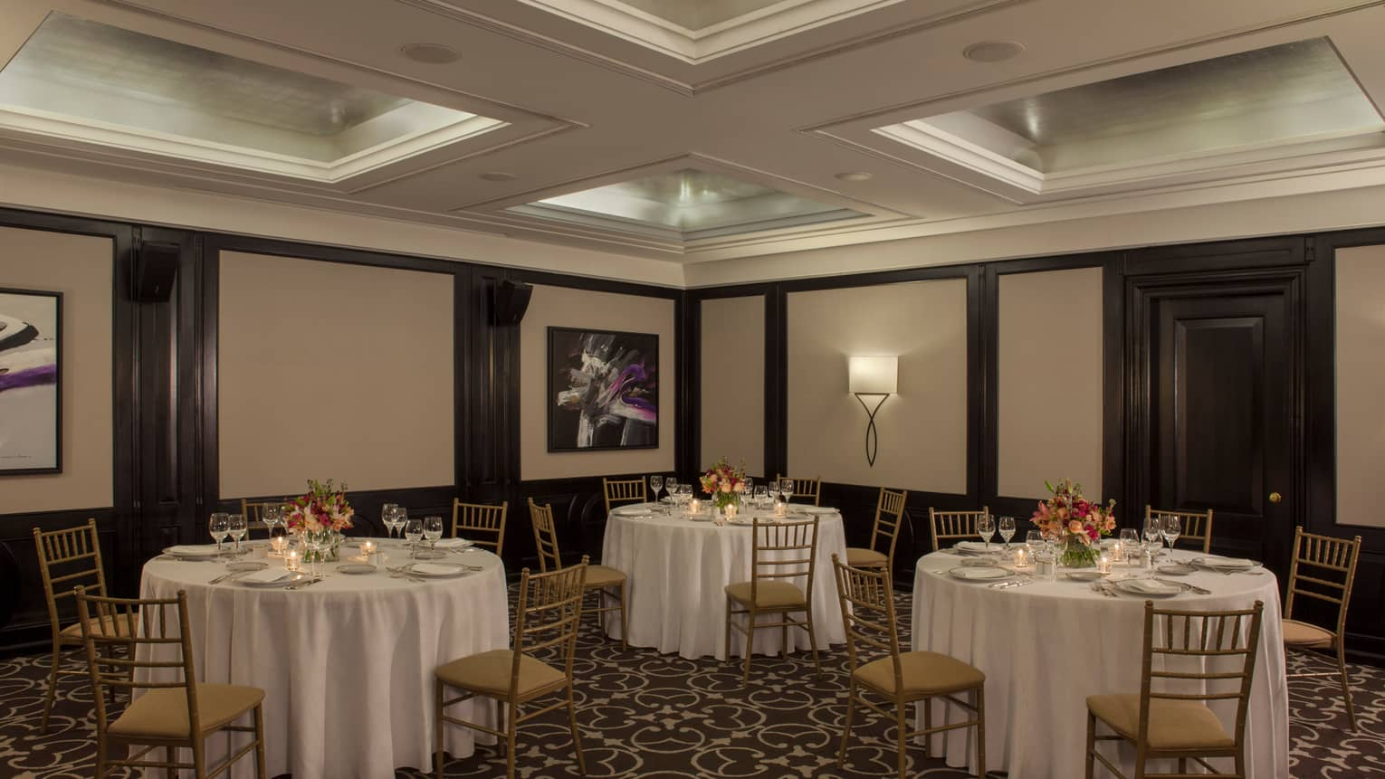 Small round banquet tables and chairs under recessed ceiling