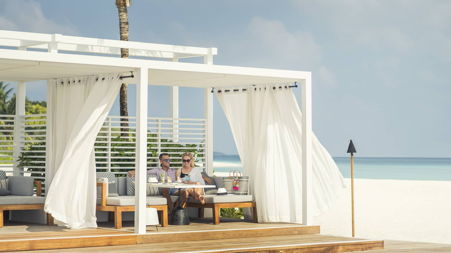 Guests enjoying cocktails and a slight breeze next to the water at a Blu Beach Club Cabana