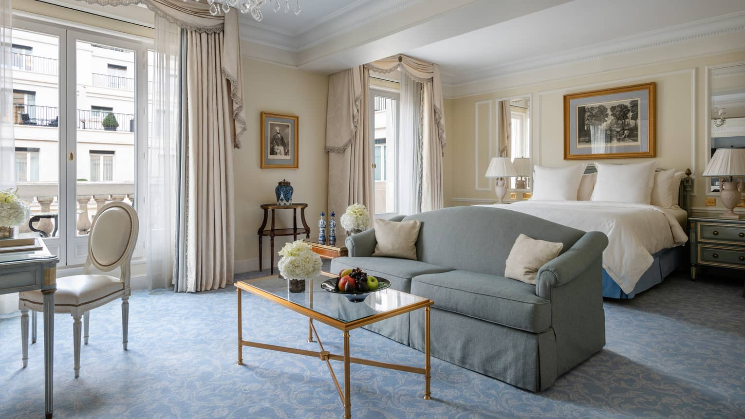 Premier room with queen bed, couch, coffee table, cream & teal Victorian accents, natural light