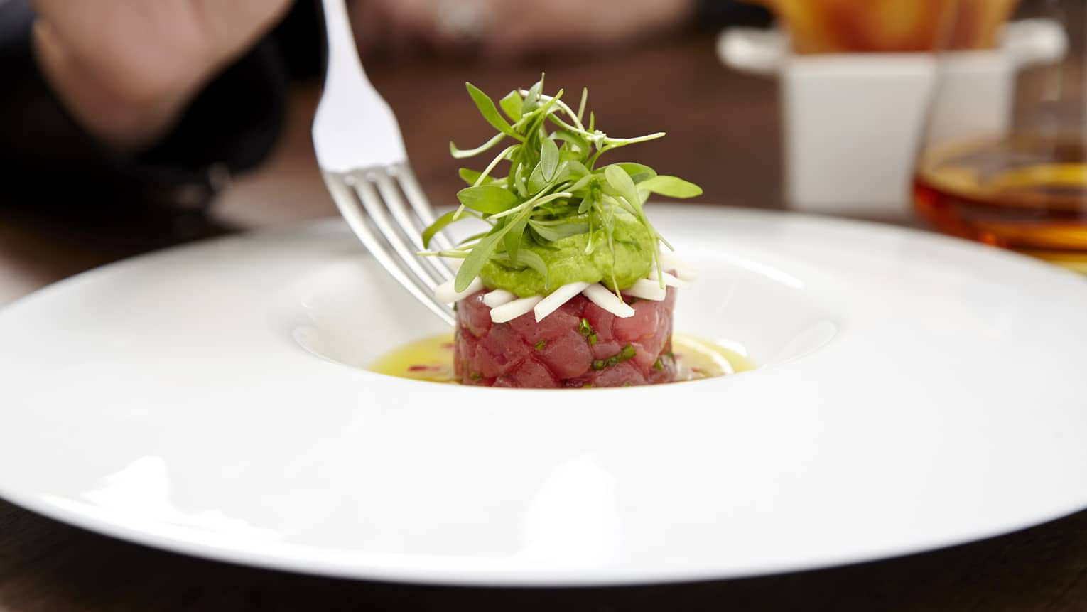 Fork over plate with small tartare topped with greens