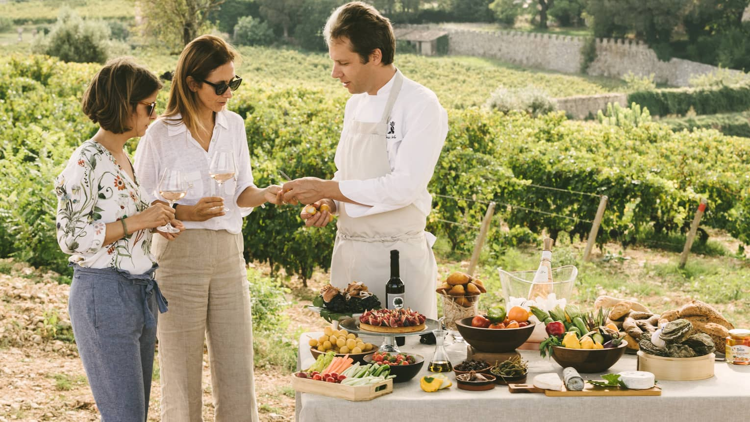 Two women hold wine glasses, stand by chef at outdoor buffet table in garden