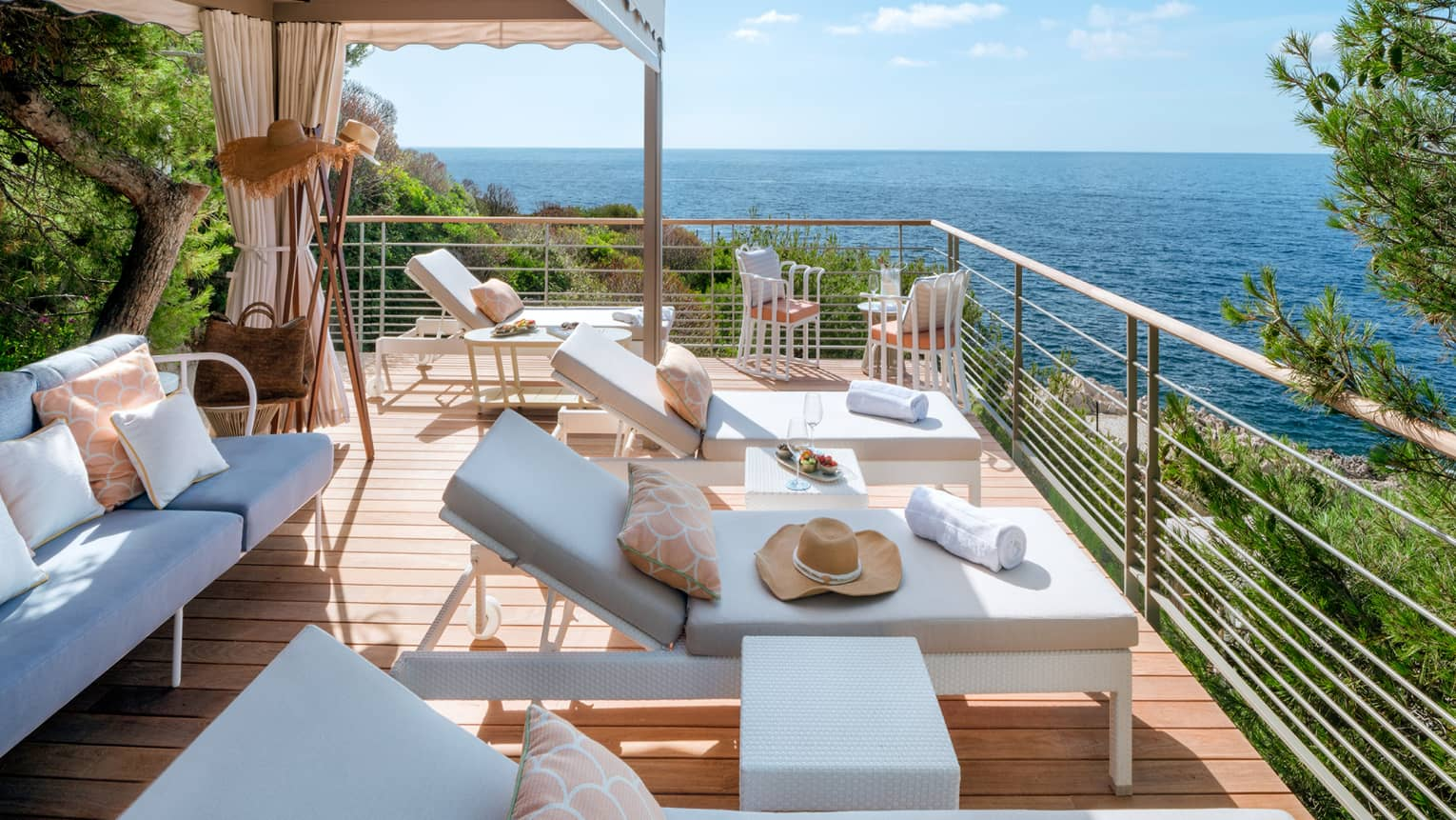 Club Dauphin private cabana terrace with white settee and lounge chairs, sea view