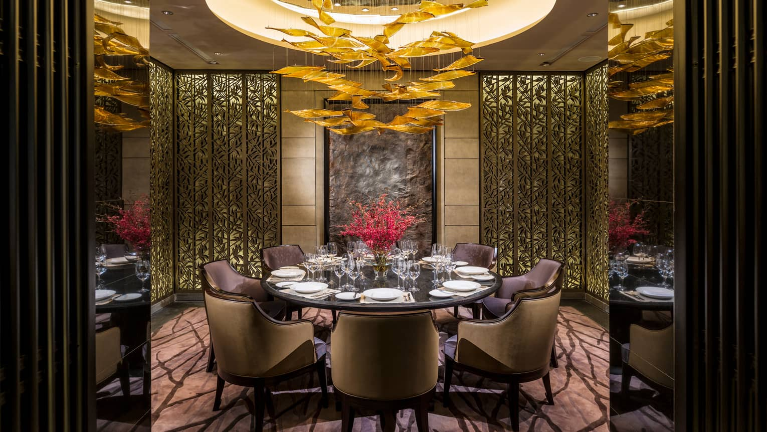 Foo restaurant round dining table in private alcove with decorative gold screens, modern chandelier
