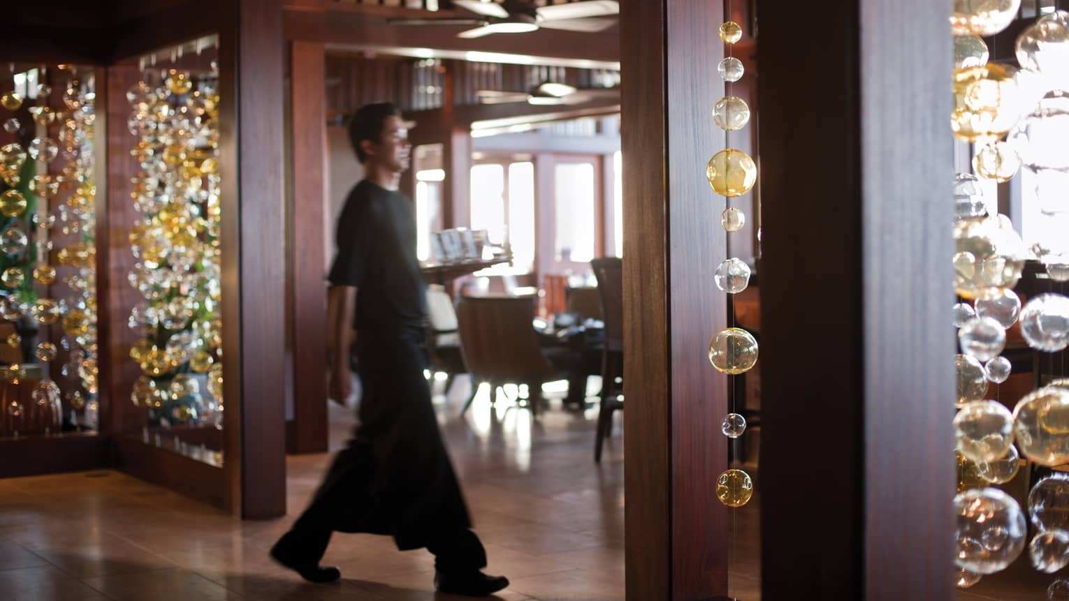 Server carries tray through ULU Sushi Lounge, past long glass bulb strings