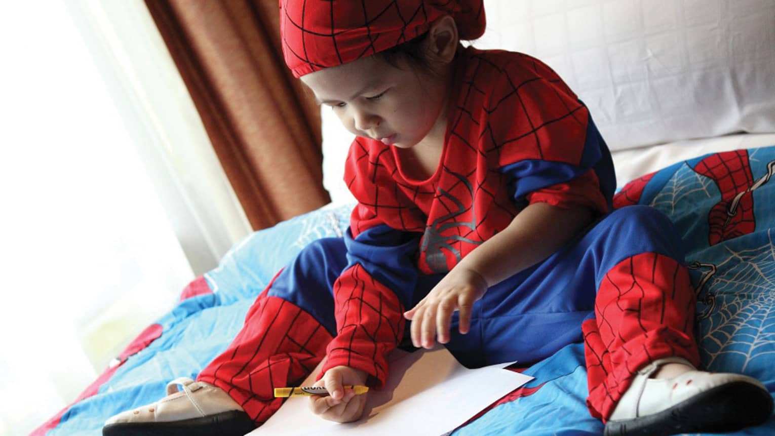 Young child wearing Spiderman costume sits on bed, colours in book