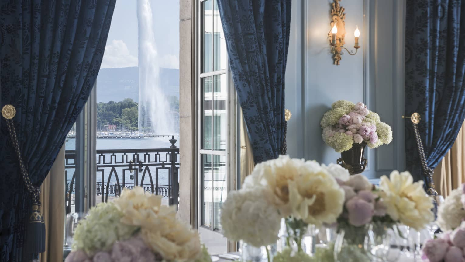 White flowers in Salon Petit Mont Blanc, open door to balcony with fountain view