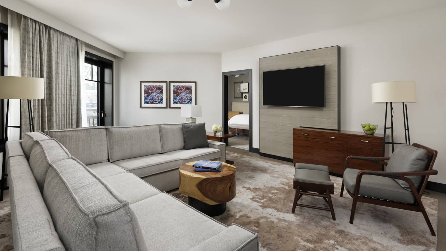 Living area in one bedroom suite with couch, chair, coffee table, and TV