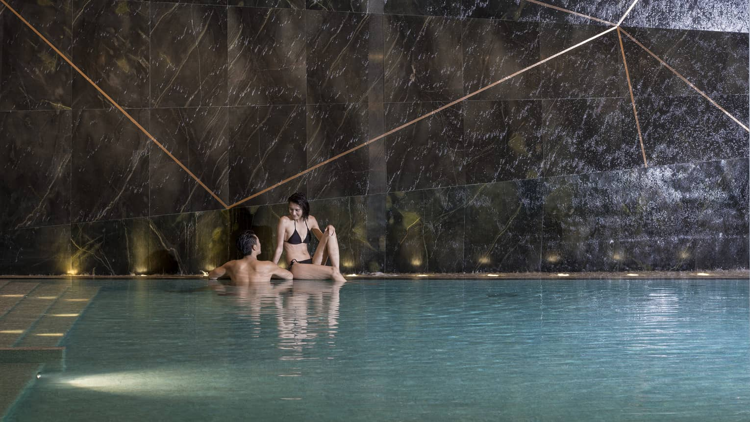 Woman sits on edge of indoor swimming pool, man wades beside her