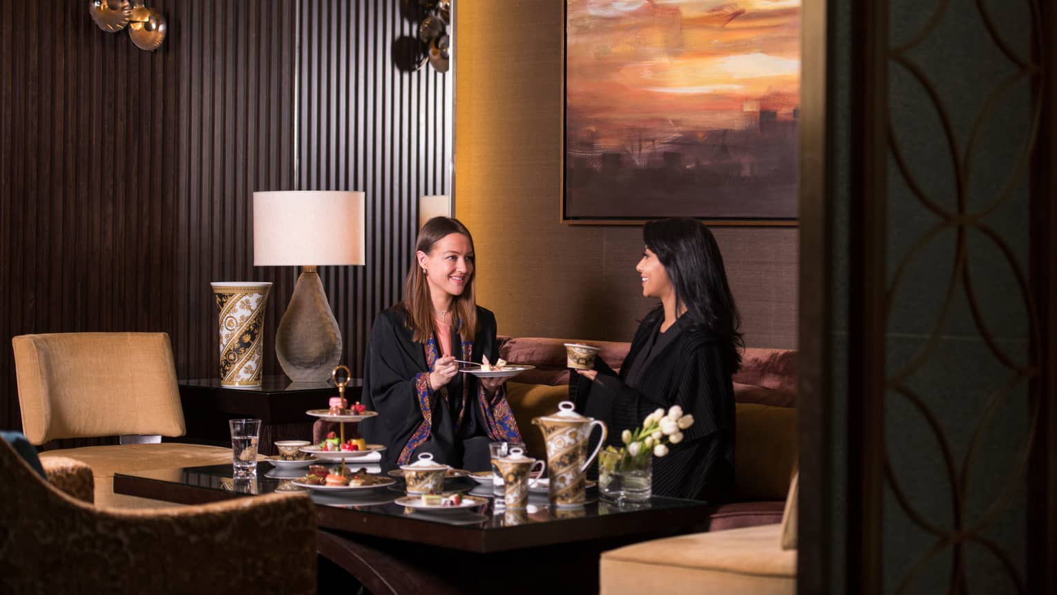 Two women in thin black robes sit on sofa, enjoy high tea at table