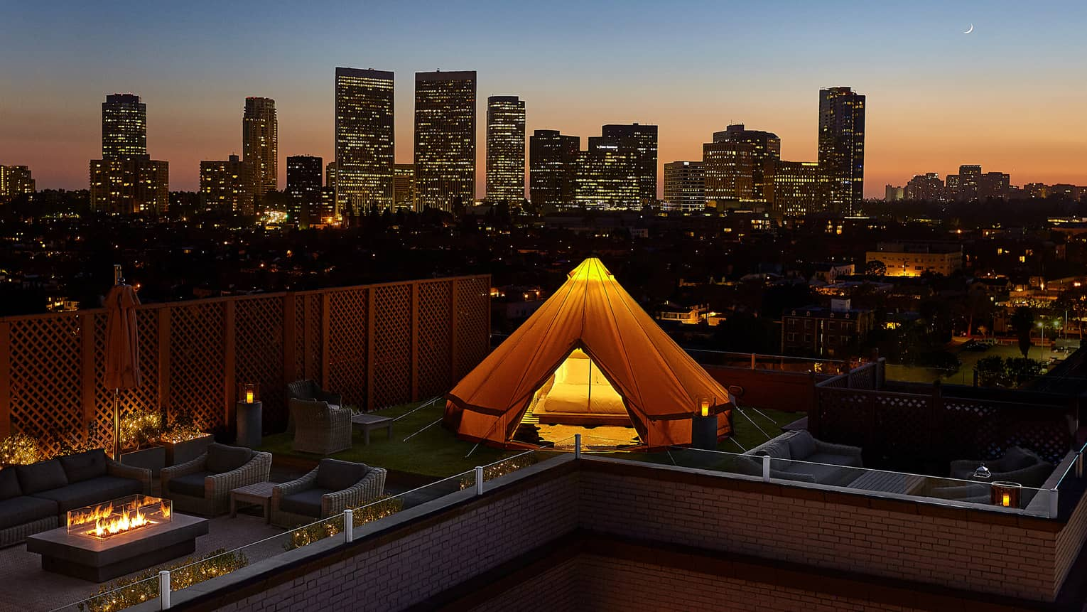 Glowing white tent, bed on rooftop patio by chairs, outdoor fireplace, Beverly Hills sunset city views