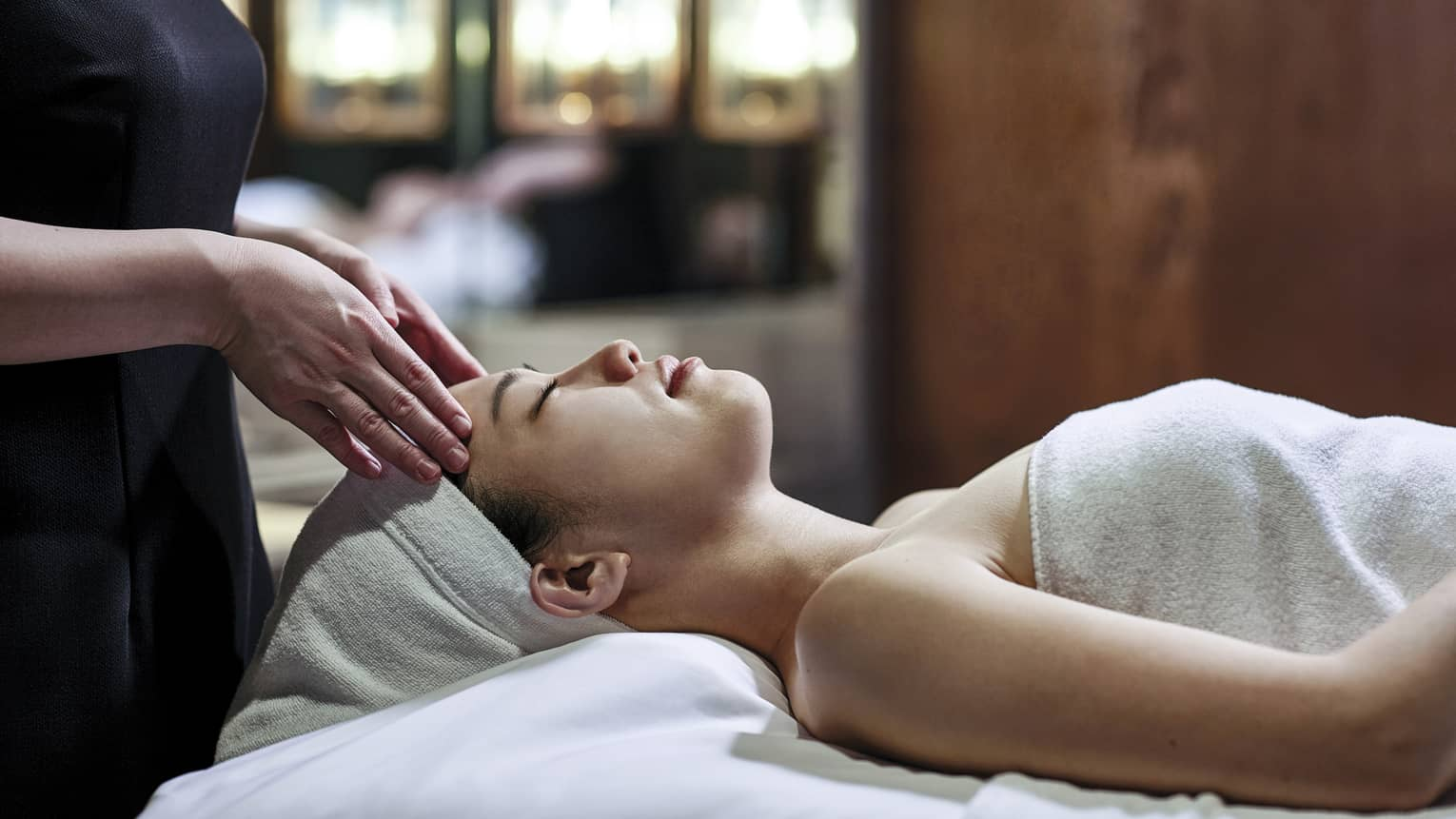 Woman getting a head massage during spa treatment, white towel over her and her head