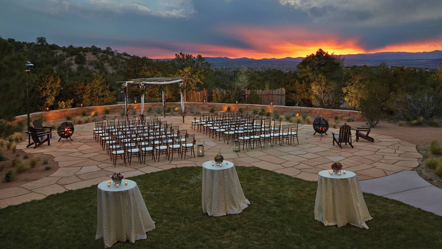 Rows of chairs on tiled surface facing wooden altar, cocktail tables overlooking trees and foothills at dusk