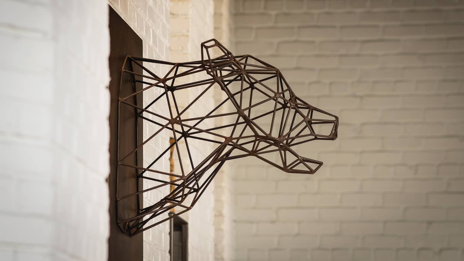 Modern wire sculpture of animal head mounted to white brick wall