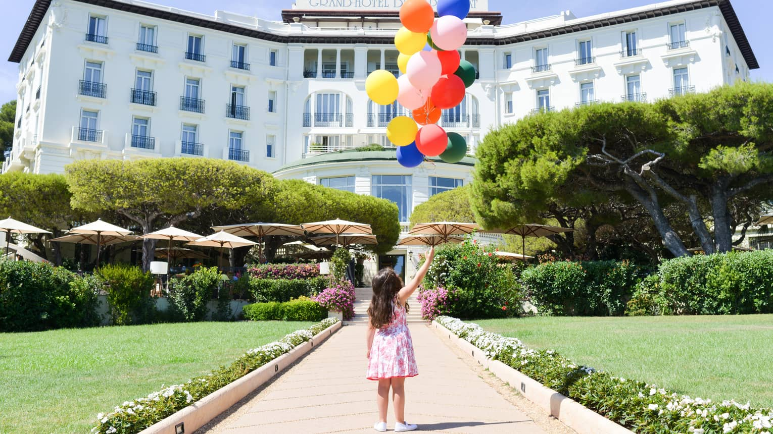 Young girl holds bunch of colourful balloons on brick path leading to hotel