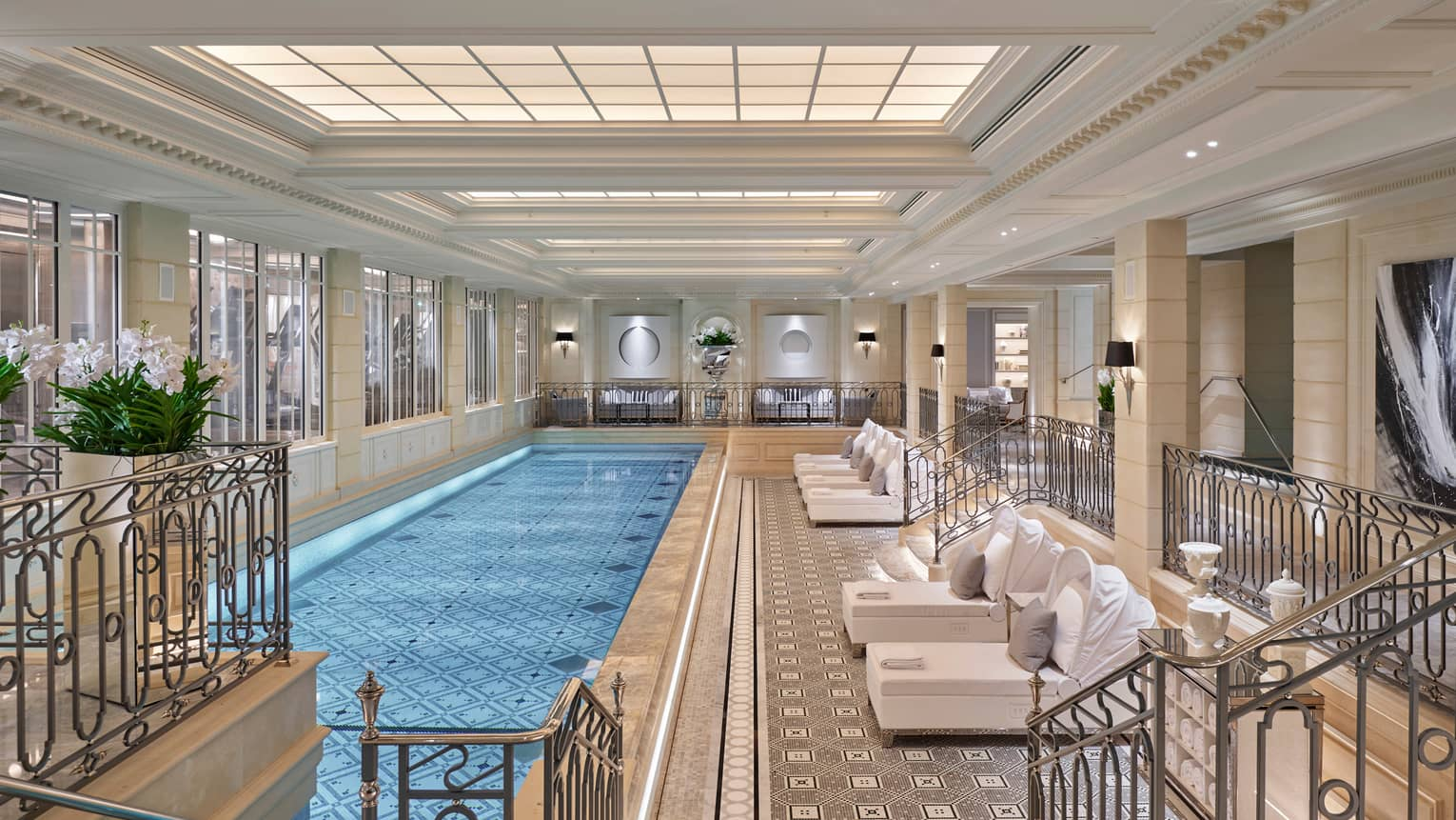 Long, elegant indoor swimming pool lined with plush white patio lounge chairs