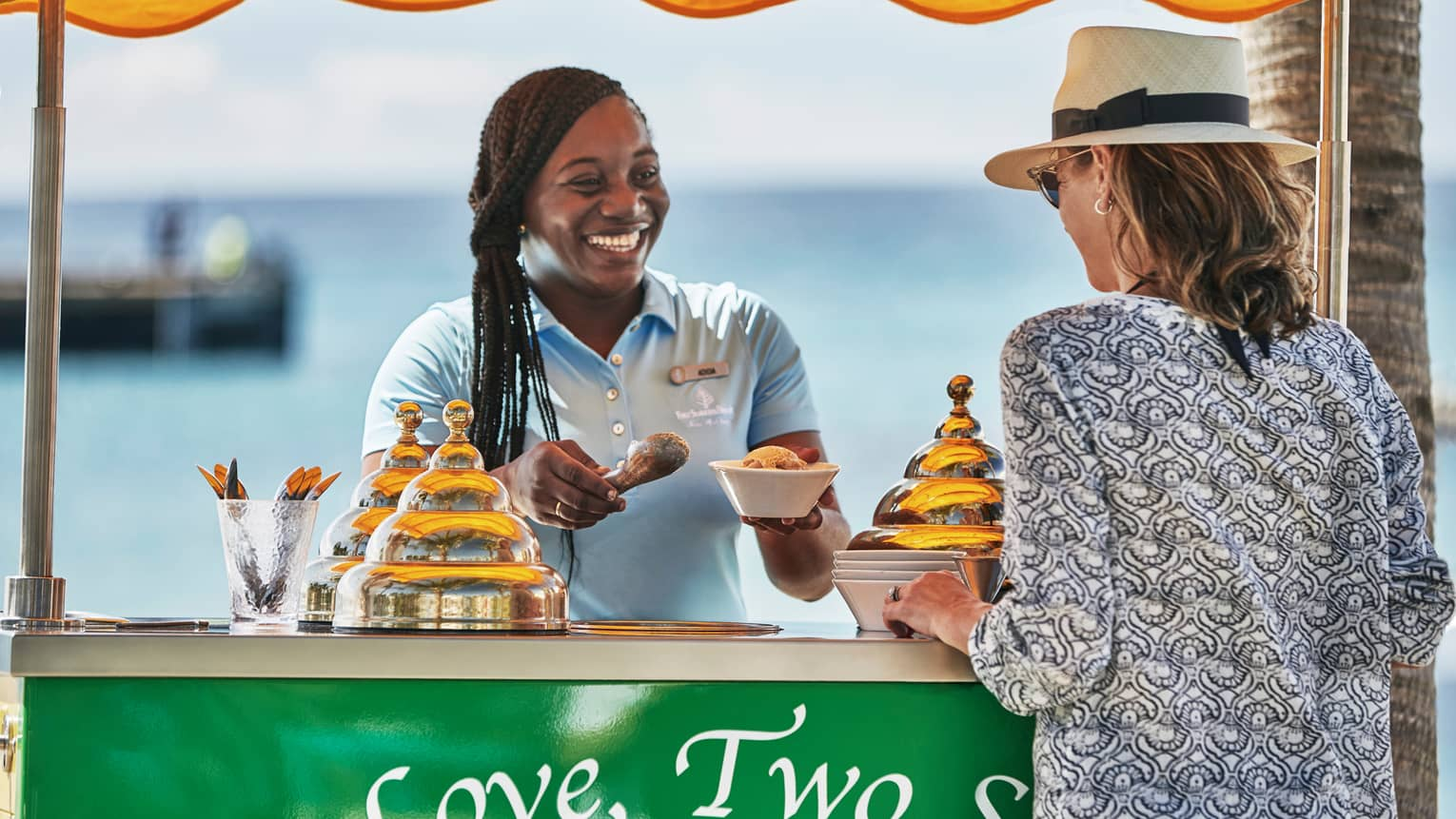 Smiling hotel staff scoops ice cream into dish for guest at beach stand