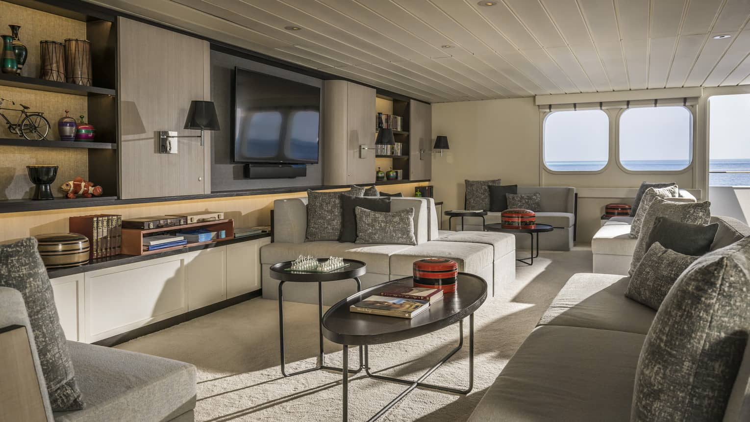 Island Explorer cruise living room with white sofas, tables, wall unit, TV