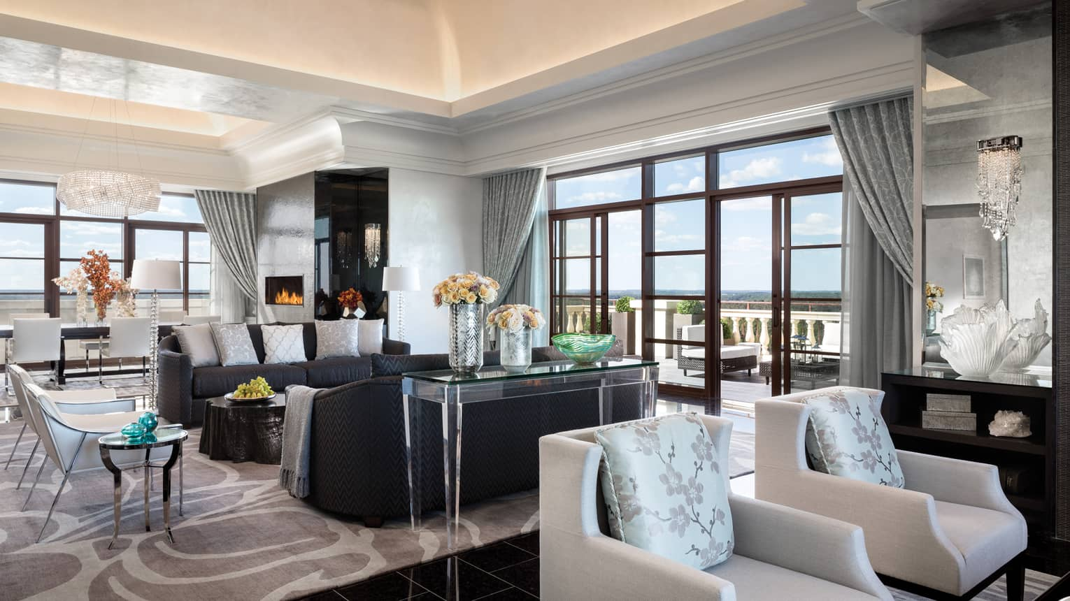 Royal Suite two seating areas in bright room under soaring ceilings, corner floor-to-ceiling windows